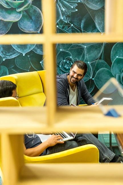 meetingsituation mit zwei Personen auf gelben Sesseln in grünem Raum